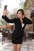 foto of selfie  - Beautiful business woman takes a selfie with her cell phone - JPG
