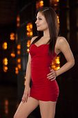 Young Woman In A Little Red Dress Poses Confidently In Front Of Amber Lights At A Club.