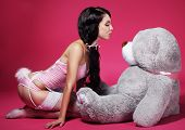 stock photo of flirtatious  - Seductive Playful Woman in Pink Lingerie with Teddy Bear - JPG