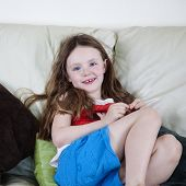 Pretty Young Girl On Sofa And Cushions - Portrait