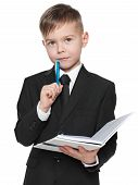 Serious Schoolboy In Black Suit With A Notebook