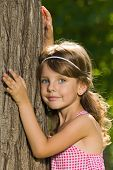 Pensive Little Girl Near A Tree