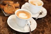 stock photo of milk  - Two white cups of Cappuccino coffee with heart shaped milk foam - JPG