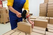 pic of dispenser  - Factory worker with packing tape gun dispenser finishing a delivery - JPG