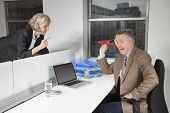 Middle-aged businessman throwing paper airplane towards female colleague in office