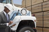 stock photo of logging truck  - African American male contractor writing notes while standing by logging truck - JPG
