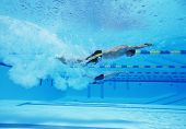 Underwater shot of three male athletes racing in swimming pool