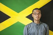 Portrait of a man with raised eyebrows against Jamaican flag