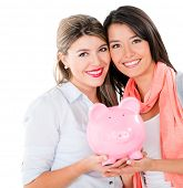 Women with their savings in a piggybank - isolated over white