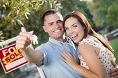 Mixed Race Excited Military Couple with New House Keys and Sold Real Estate Sign Outside.