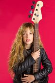 Blond Rock and roll girl bass guitar player portrait on red background