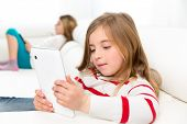 Children sister friends kid girls playing with tablet pc on white sofa