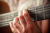 Closeup on a woman's hand playing guitar