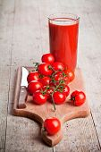 tomato juice in glass and fresh tomatoes on wooden board