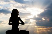 A silhouette of a woman sitting in yoga position, meditating against sunset sky. Zen, meditation