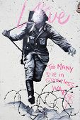 BERLIN GERMANY - 18 NOVEMBER 2013:Graffiti on a wall in Berlin depicting a Nazi soldier, with the slogan 'too many die in senseless wars', Hannah-Arendt Strasse, Berlin, Germany
