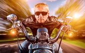 Biker man wearing a leather jacket and sunglasses sitting on his motorcycle looking at the sunset, racing on the road. Filter applied in post-production.