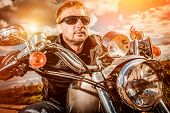 Biker man wearing a leather jacket and sunglasses sitting on his motorcycle looking at the sunset. Filter applied in post-production. Filter applied in post-production.