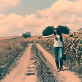 Girl hitch-hikes with retro suitcase in countryside. Young woman traveling, image toned.