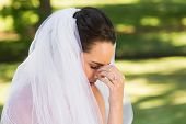 Close-up side view of a beautiful worried bride at the park