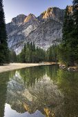Morning sun shining on Glacier Point from the Merced river. Yosemite National Park, California, USA
