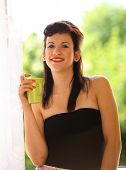 Beautiful Girl Drinking Tea Or Coffee Indoor. Green Blurred Background