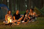 stock photo of tent  - Friends camping in forest together and having fun - JPG