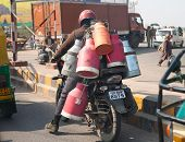 INDIA- JANUARY 28: The man on the motorcycle with cans behind the back on the road on January 28 201