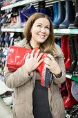 Woman With Red Waterproof Shoes In Hands Buying In The Shop