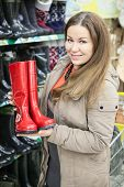 Smiling Woman Holding Red Watertights When Buying In Shop