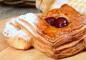Roll from flaky pastry with cherry close-up