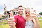 Happy Travel couple in Rome by Coliseum showing thumbs up hand sign looking at camera cheerful. Two