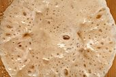 Rising Yeast Dough on wooden table surface top view texture