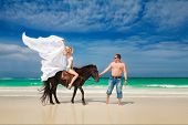 Young Couple In Love Walking With The Horse On A Tropical Beach. Tropical Sea In The Background. Sum