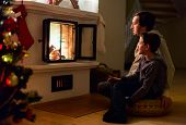 Father and his son sitting by a fireplace in their family home on Christmas eve