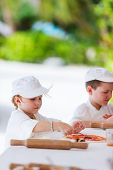 Adorable little girl and cute boy dressed as chefs making pizza