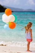 Back view of little girl with colorful balloons at beach during summer vacation