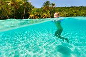 Split underwater photo of adorable little girl with blue inflatable ring swimming in tropical ocean
