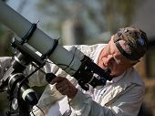 Senior Man Setting Up A Telescope