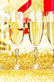Glasses of champagne and red ribbons on golden background