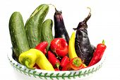 A bowl of Fresh Picked home grown Red and Yellow Peppers, Purple Egg Plant, and Green Cucumber, isol