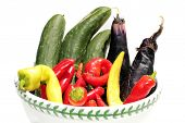 A bowl of Fresh Picked home grown Red and Yellow Peppers, Purple Egg Plant, and Green Cucumber, isolated on white with room for your text. The perfect bowl of home grown veggies for all your needs.