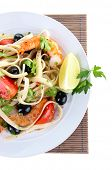 Fresh prawns with spaghetti, olives, tomatoes and parsley in a big round plate on a napkin on white