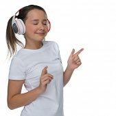 Attractive little girl enjoying her music on headphones standing with her eyes closed in bliss marki