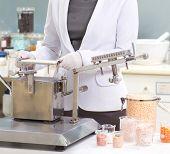 pharmacist preparing medication with packaging capsule machine