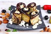 Fried aubergine with cottage cheese in a square plate on wooden background