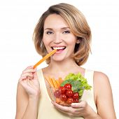 Beautiful young healthy woman eating a salad - isolated on white.