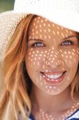 Portrait of smiling woman in sunhat