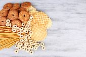 Biscuits, dry breakfast and sticks scattered on wooden background