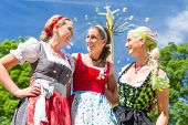 Women friends visiting Bavarian folk festival in  Dirndl standing in front of carousel